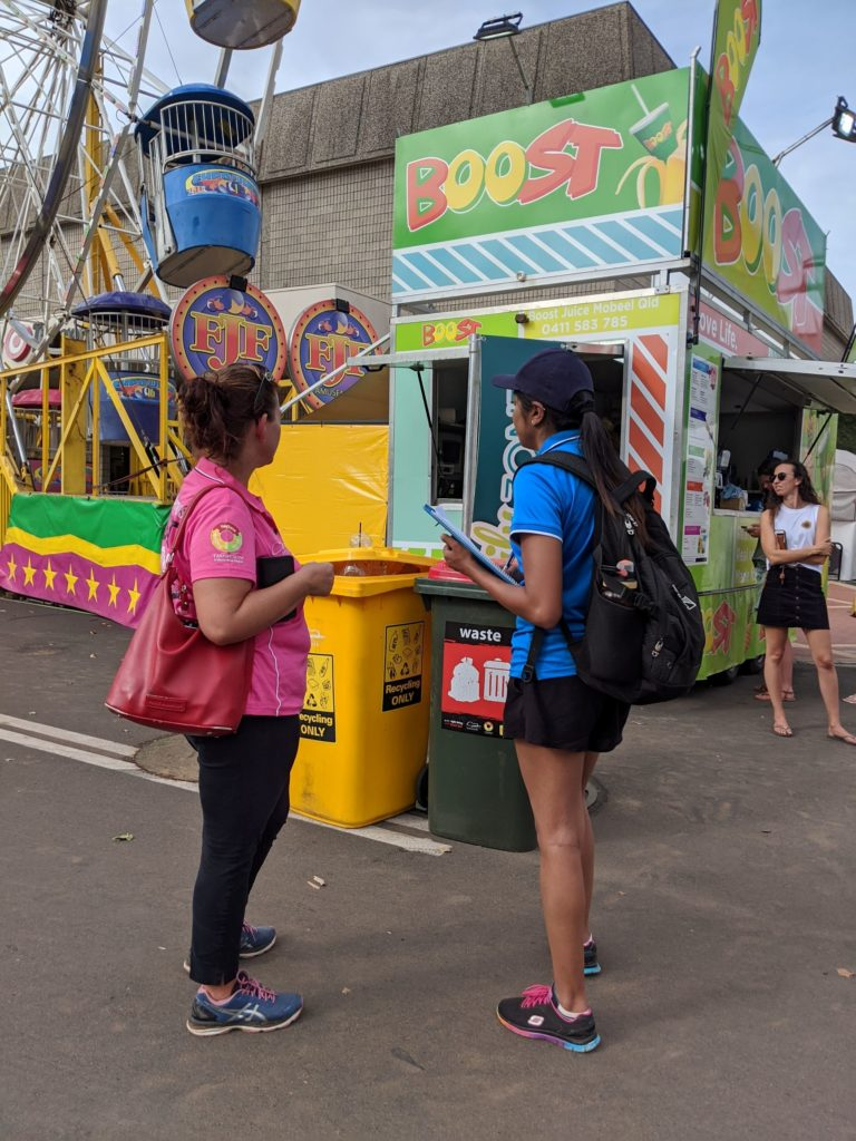 Resource Recovery Officer Priya having a chat about recycling with an engaged festival goer