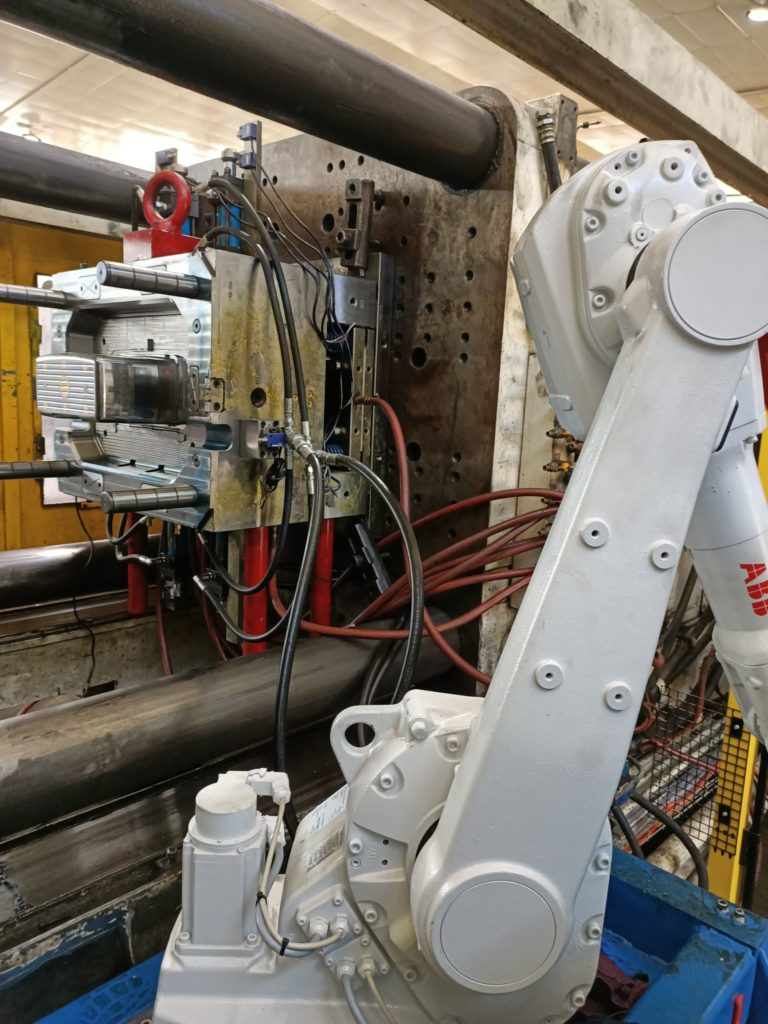 Robot getting ready to place window for moulding into a sharps container base