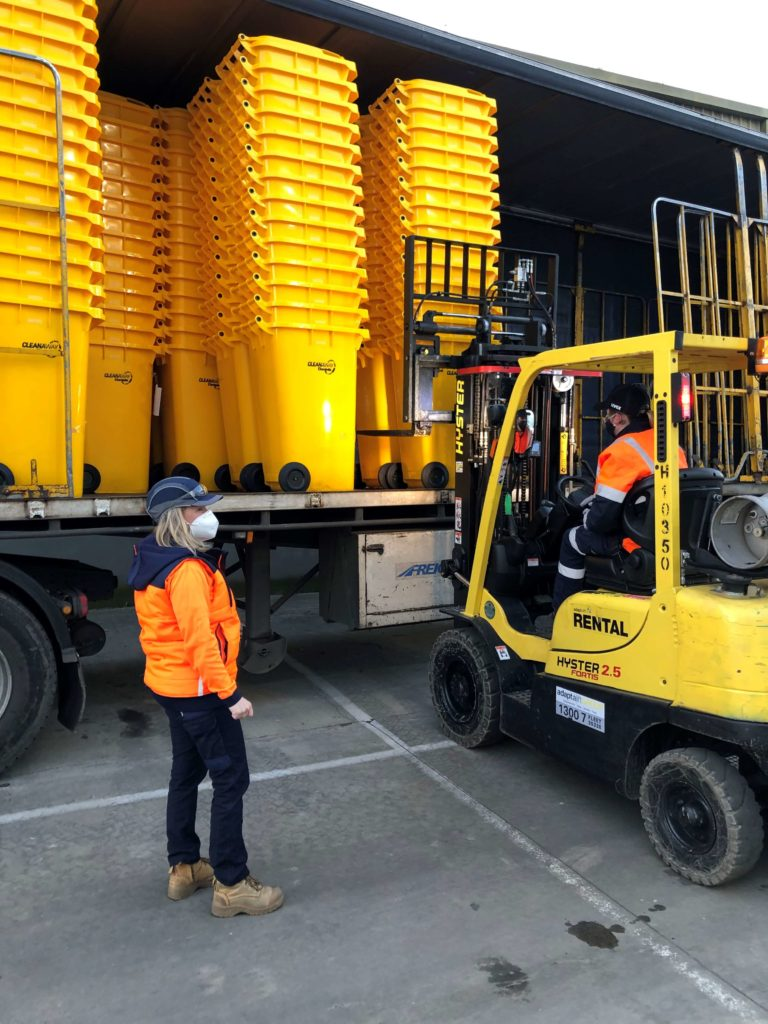 Clinical waste containers being loaded onto semi-trailers for delivery to healthcare facilities
