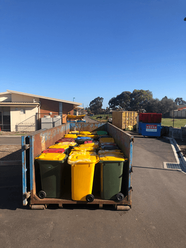 Wheelie bins loaded into a skip to support collection and delivery